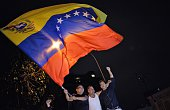 TOPSHOT Venezuelan opposition supporters celebrate the results of the legislative election in Caracas on the early morning December 7 2015...