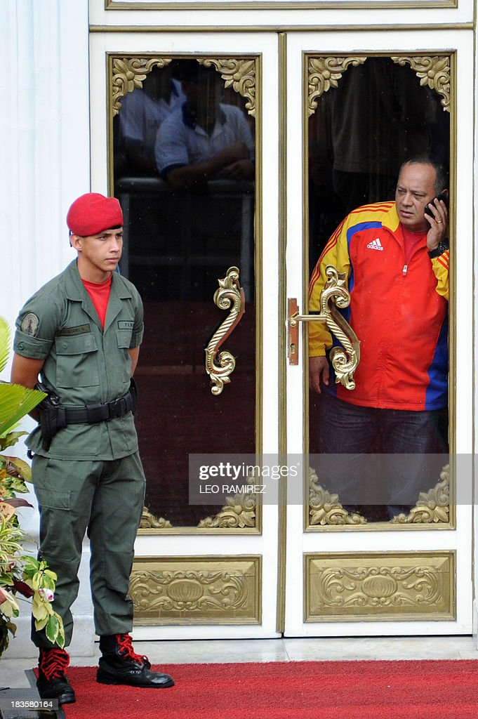 Venezuelan Parliament President Diosdado Cabello speaks on his mobile phone in Miraflores presidential palace before the start of a ceremony commemorating late President Hugo Chavez re election, in Caracas on October 7, 2013. AFP PHOTO/Leo RAMIREZ