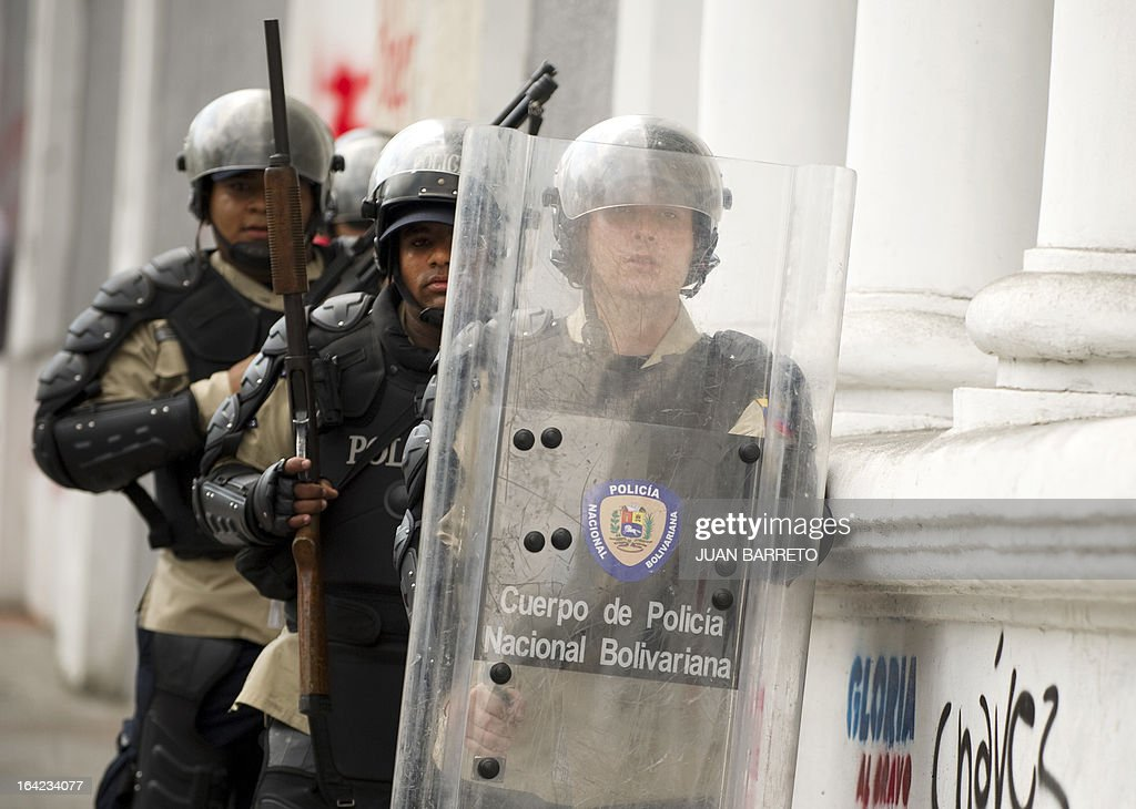 Venezuelan policemen in riot gear defilade themselves in downtown Caracas on March 21, 2013 during a demonstration of opposition students demanding to the National Electoral Council (CNE) transparency during the presidential elections next February 14.