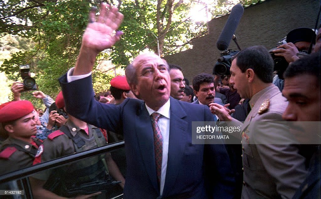 Venezuelan President Carlos Andres Perez is flanked by security agents as he waves to supporters 06 December 1992 after casting his vote for the...