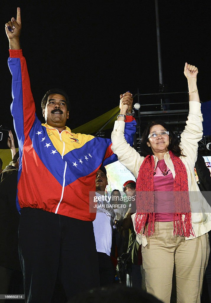 Venezuelan President elect Nicolas Maduro (L) celebrates with his wife Cilia Flores after knowing the election results in Caracas on April 14, 2013. Venezuela's acting President Nicolas Maduro declared victory on Sunday in the race to succeed late leader Hugo Chavez after the electoral council announced that he had won in a close battle. AFP PHOTO/Juan BARRETO