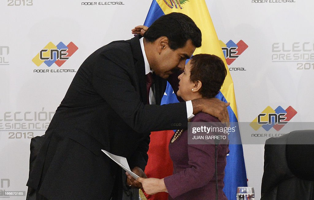 Venezuelan President elect Nicolas Maduro (L) embraces the president of the national electoral council, Tbisay Lucena, in Caracas on April 15, 2013. Venezuela's electoral authorities on Monday confirmed acting President Nicolas Maduro as the winner of the weekend election to succeed Hugo Chavez, despite opposition demands for a recount. BARRETO