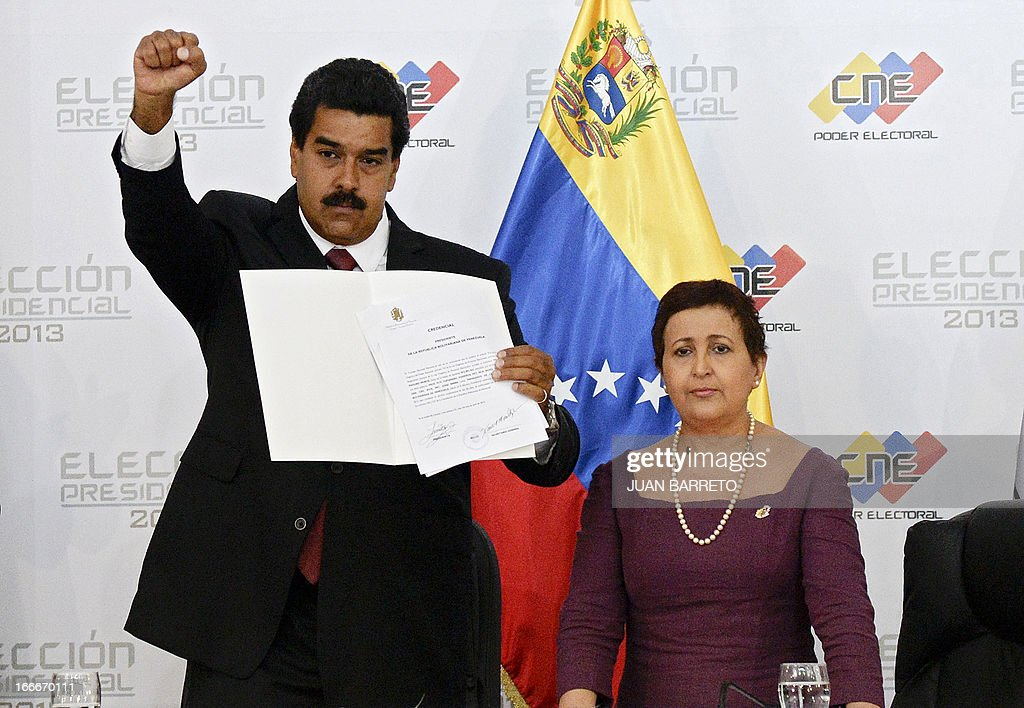 Venezuelan President elect Nicolas Maduro (L) raises his fist as he shows a document delivered by the president of the national electoral council, Tibisay Lucena, in Caracas on April 15, 2013. Venezuela's electoral authorities on Monday confirmed acting President Nicolas Maduro as the winner of the weekend election to succeed Hugo Chavez, despite opposition demands for a recount. BARRETO