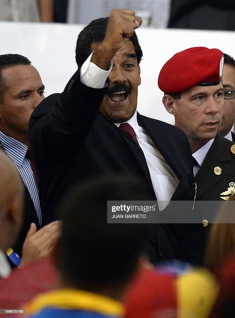 Venezuelan President elect Nicolas Maduro (C) raises his fist before receiving a document from the national electoral council, in Caracas on April 15, 2013. Venezuela's electoral authorities on Monday confirmed acting President Nicolas Maduro as the winner of the weekend election to succeed Hugo Chavez, despite opposition demands for a recount.