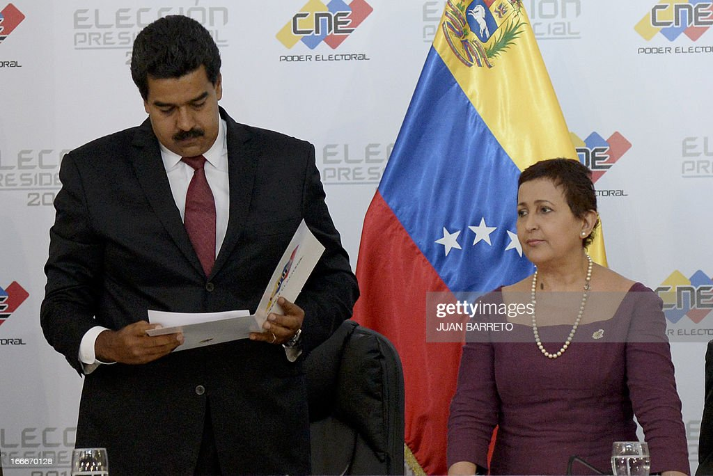 Venezuelan President elect Nicolas Maduro (L) reads a document delivered by the president of the national electoral council, Tbisay Lucena, in Caracas on April 15, 2013. Venezuela's electoral authorities on Monday confirmed acting President Nicolas Maduro as the winner of the weekend election to succeed Hugo Chavez, despite opposition demands for a recount. BARRETO