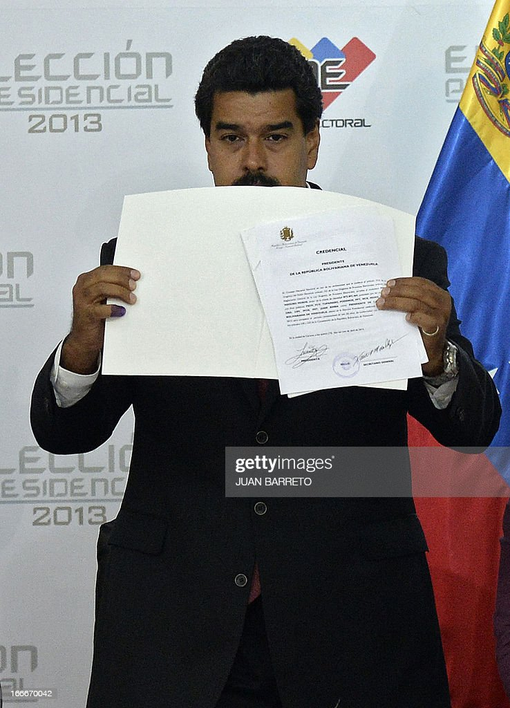 Venezuelan President elect Nicolas Maduro shows a document delivered by the national electoral council, in Caracas on April 15, 2013. Venezuela's electoral authorities on Monday confirmed acting President Nicolas Maduro as the winner of the weekend election to succeed Hugo Chavez, despite opposition demands for a recount. BARRETO