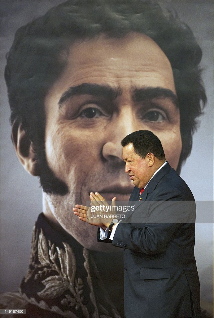 Venezuelan President Hugo Chavez applauds in front of a picture showing the possible face of Liberator Simon Bolivar --a digital rendering from genetic data, following the exumation of Bolivar´s remains in 2010-- during celebrations of Bolivar's brithday in Caracas on July 24, 2012.