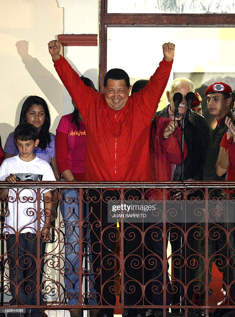Venezuelan President Hugo Chavez (C) gestures while speaking to supporters after receiving news of his reelection in Caracas on October 7, 2012. According to the National Electoral Council, Chavez was reelected with 54.42% of the votes, beating opposition candidate Henrique Capriles, who obtained 44.47%.