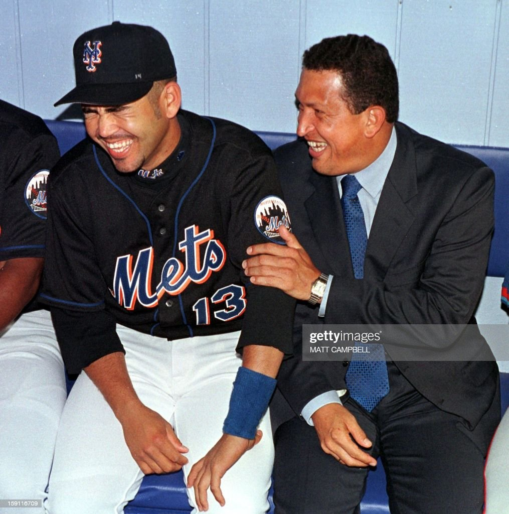 Venezuelan President Hugo Chavez (R) laughs with fellow Venezuelan and New York Mets second baseman Edgardo Alfonso (L) in the dugout 09 June, 1999 before the Mets game against the Blue Jays at Shea Stadium in Flushing, NY. Chavez threw out the ceremonial first pitch at the beginning of the game. AFP PHOTO/Matt CAMPBELL