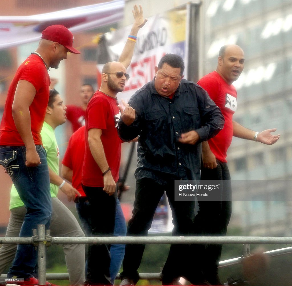 Venezuelan President Hugo Chavez plays air guitar with a group of artist -from left- El Potro Alvarez, Hany Kauam, Omar Enrique and members of Los Cadillacs for a campaign rally on Thursday, October 4, 2012.