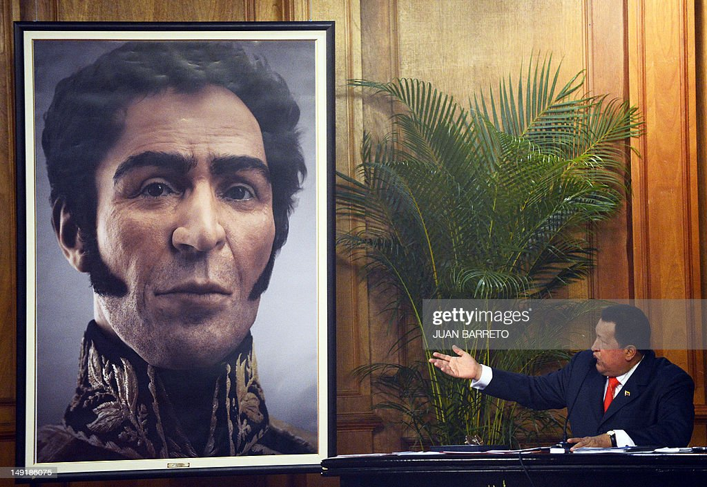 Venezuelan President Hugo Chavez (R) shows a picture showing the possible face of Liberator Simon Bolivar --a digital rendering from genetic data, following the exumation of Bolivar remains in 2010-- during celebrations of Bolivar's brithday in Caracas on July 24, 2012.