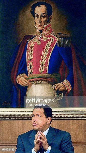 Venezuelan President Hugo Chavez speaks beneath a portrait of South American liberator Simon Bolivar 05 December 2001 in Caracas Venezuela's largest...