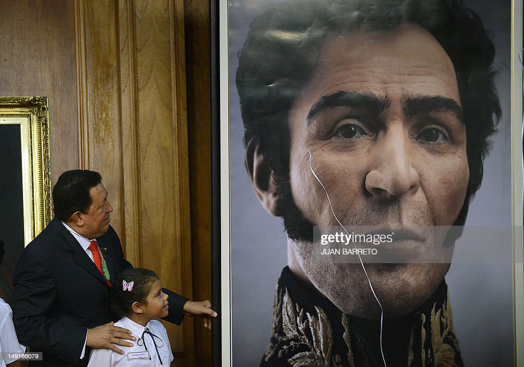 Venezuelan President Hugo Chavez (L) unveils a picture showing the possible face of Liberator Simon Bolivar --a digital rendering from genetic data, following the exumation of Bolivar remains in 2010-- during celebrations of Bolivar's brithday in Caracas on July 24, 2012.