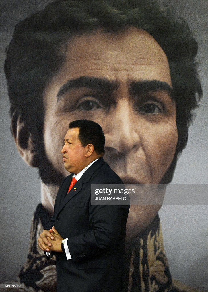 Venezuelan President Hugo Chavez walks in front of a picture showing the possible face of Liberator Simon Bolivar --a digital rendering from genetic data, following the exumation of Bolivar remains in 2010-- during celebrations of Bolivar's brithday in Caracas on July 24, 2012.