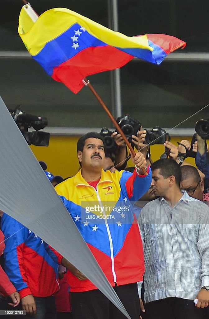 Venezuelan President in Charge Nicolas Maduro waves a national flag as he officially registers his candidacy for the upcoming presidential election at the National Electoral Council (SNE) in Caracas, on March 11, 2013. Venezuela has entered a bitter election race to succeed Hugo Chavez, with his chosen successor branding his challenger a 'fascist' after the opposition candidate accused him of exploiting the late leader's death. AFP PHOTO/Luis Acosta