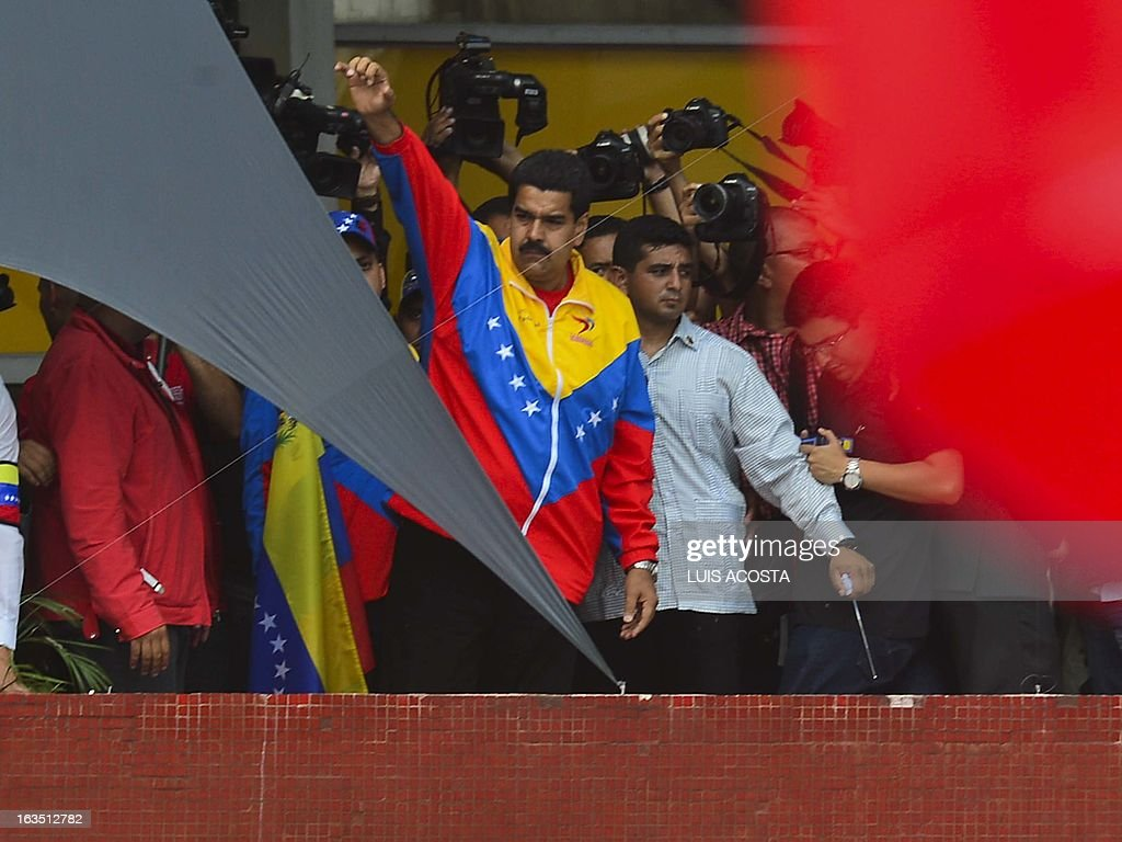 Venezuelan President in Charge Nicolas Maduro waves at the crowd as he officially registers his candidacy for the upcoming presidential election at the National Electoral Council (SNE) in Caracas, on March 11, 2013. Venezuela has entered a bitter election race to succeed Hugo Chavez, with his chosen successor branding his challenger a 'fascist' after the opposition candidate accused him of exploiting the late leader's death. AFP PHOTO/Luis Acosta
