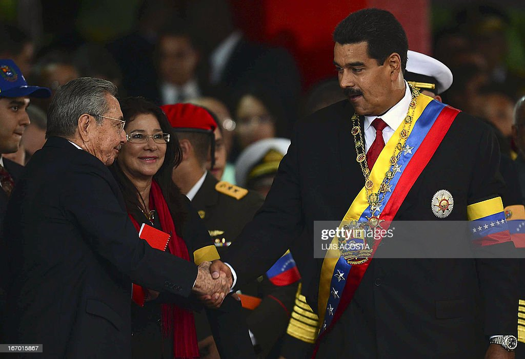 Venezuelan President Nicolas Maduro (R) and Cuba's Raul Castro shake hands during a ceremony after his installation in Caracas on April 19, 2013. AFP PHOTO/Luis Acosta