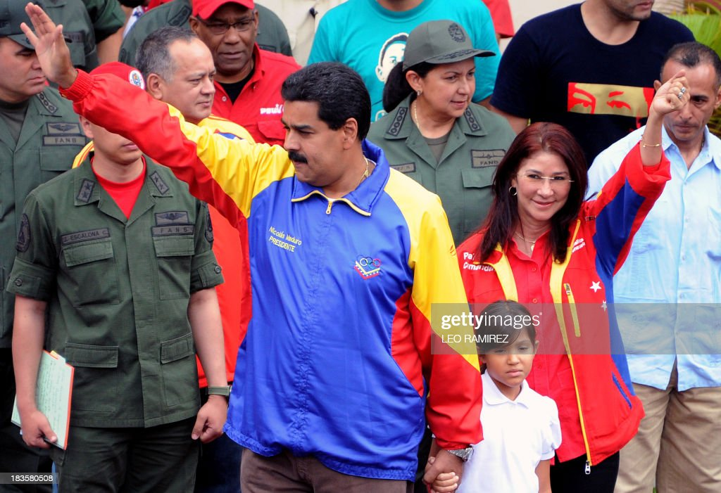 Venezuelan President Nicolas Maduro (L) and First Lady Cilia Flores (R) wave to supporters during a ceremony commemorating late President Hugo Chavez re election, in Caracas on October 7, 2013. AFP PHOTO/Leo RAMIREZ