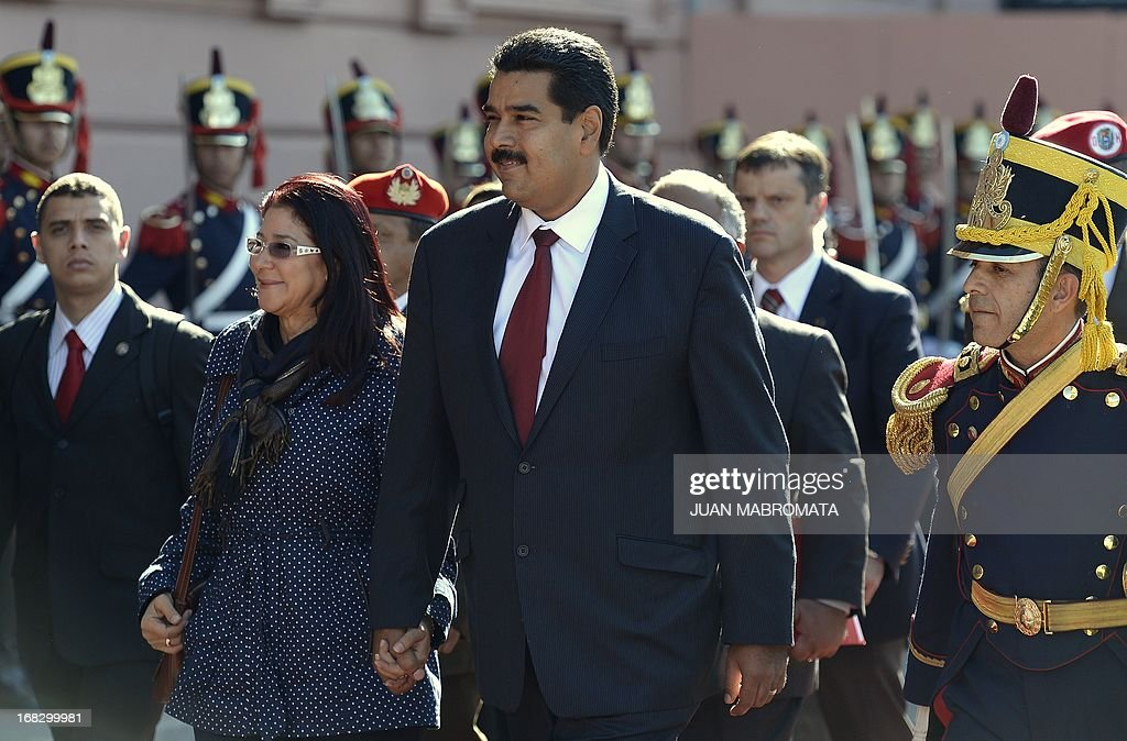 Venezuelan President Nicolas Maduro (C) and his wife Cilia Flores (L) arrive at the Government Palace in Buenos Aires on May 8, 2013. Maduro arrived today from Uruguay and afterwards will travel to Brazil. AFP PHOTO / Juan Mabromata