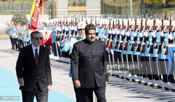 Venezuelan President Nicolas Maduro and Turkish President Recep Tayyip Erdogan walk past honor guard during an official welcome ceremony at...