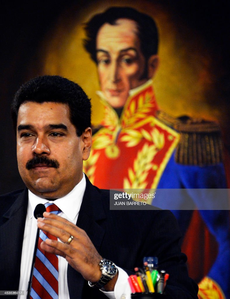 Venezuelan President Nicolas Maduro delivers a speech after receiving from the National Assembly the new law 'Plan de la Patria'--presented by the late president Hugo Chavez during the 2012 presidential campaign-- at the Miraflores presidential palace, in Caracas on December 4, 2013. AFP PHOTO/JUAN BARRETO