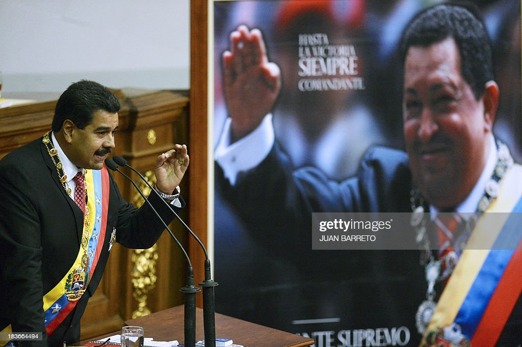 Venezuelan President Nicolas Maduro delivers a speech at the National Assembly next to a portrait of former Venezuelan President Hugo Chavez (1954-2013), in Caracas on October 8, 2013, before signing the draft of a law which would enable him to have superpowers. The law 'will be an instrument for the politic and economic offensive of the New Stage of the Revolution', Maduro said. AFP PHOTO/JUAN BARRETO