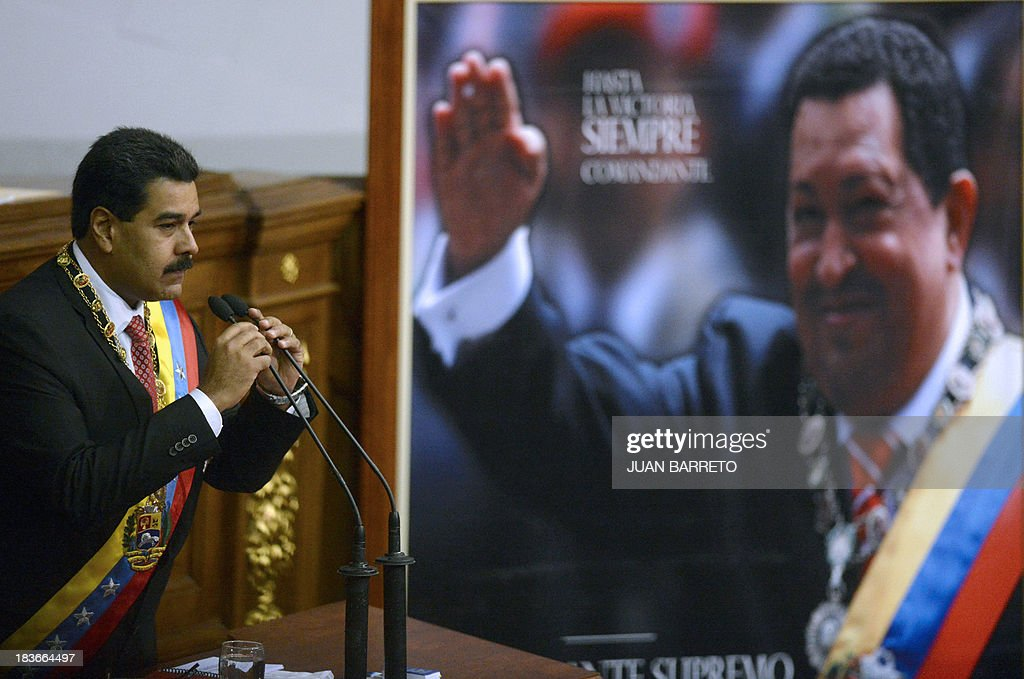 Venezuelan President Nicolas Maduro delivers a speech at the National Assembly next to a portrait of former Venezuelan President Hugo Chavez (1954-2013), in Caracas on October 8, 2013, before signing the draft of a law which would enable him to have superpowers. The law 'will be an instrument for the politic and economic offensive of the New Stage of the Revolution', Maduro said.