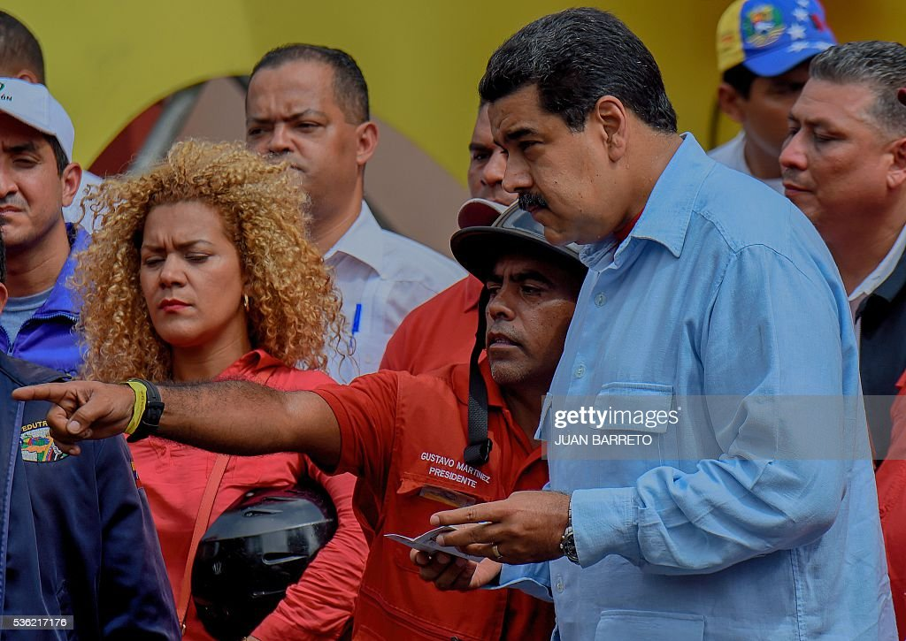 Venezuelan President Nicolas Maduro (R) during a rally in Caracas on May 31, 2016. Venezuelan President Nicolas Maduro called for a 'national rebellion' against alleged international threats Tuesday and told the head of the Organization of American States to 'shove it' in an escalating war of words. / AFP / JUAN