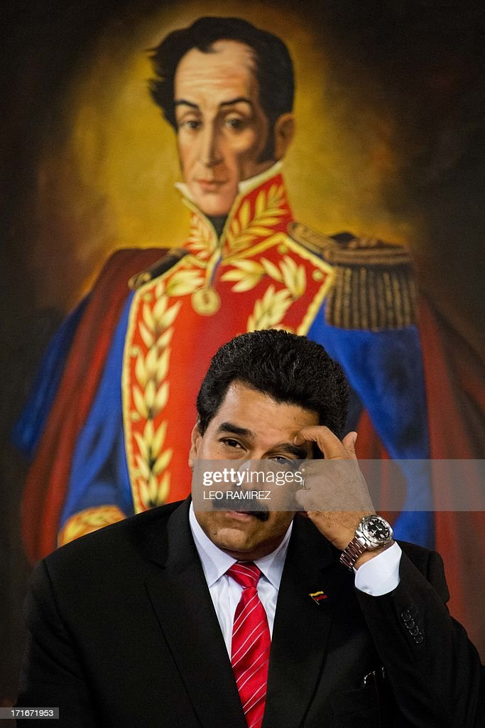 Venezuelan President Nicolas Maduro gestures during the ceremony to posthumously grant former President Hugo Chavez the National Journalism award, at the Miraflores presidential palace in Caracas on June 27, 2013. AFP PHOTO/Leo RAMIREZ