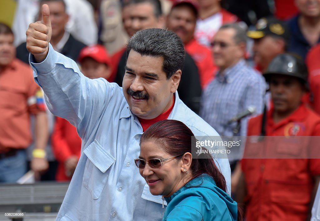 Venezuelan President Nicolas Maduro (L) gives the thumb up next to First Lady Cilia Flores during a rally in Caracas on May 31, 2016. Venezuelan President Nicolas Maduro called for a 'national rebellion' against alleged international threats Tuesday and told the head of the Organization of American States to 'shove it' in an escalating war of words. / AFP / JUAN