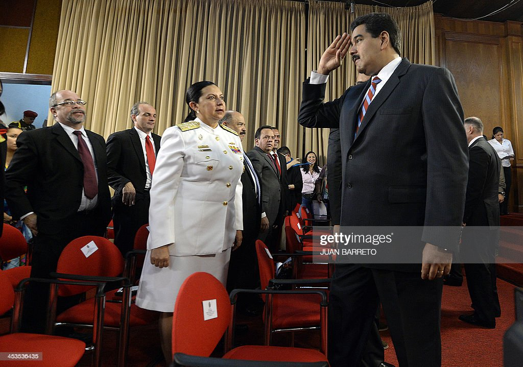 Venezuelan President Nicolas Maduro (R) greets ministers before receiving from the National Assembly the new law 'Plan de la Patria'--presented by the late president Hugo Chavez during the 2012 presidential campaign-- at the Miraflores presidential palace, in Caracas on December 4, 2013. AFP PHOTO/JUAN BARRETO