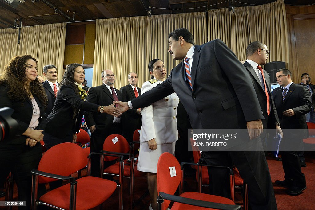 Venezuelan President Nicolas Maduro (R) greets ministers before receiving from the National Assembly the new law 'Plan de la Patria'--presented by the late president Hugo Chavez during the 2012 presidential campaign-- at the Miraflores presidential palace, in Caracas on December 4, 2013.