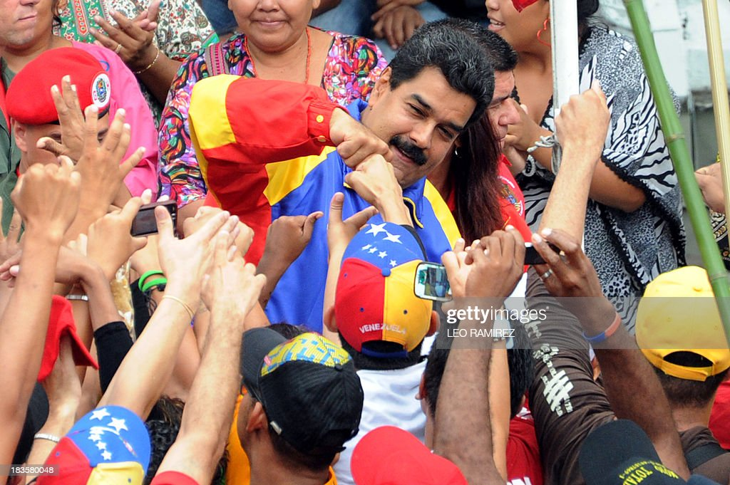 Venezuelan President Nicolas Maduro greets supporters during a ceremony commemorating late President Hugo Chavez re election, in Caracas on October 7, 2013. AFP PHOTO/Leo RAMIREZ