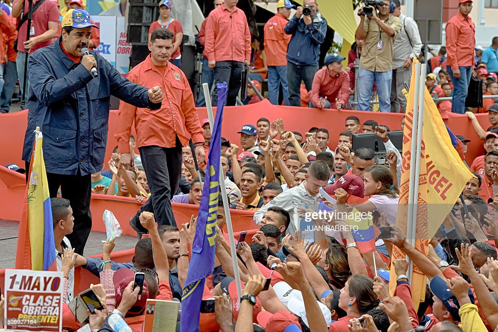 Venezuelan president Nicolas Maduro (L) greets supporters during a march to mark International Workers' Day, in Caracas on May 1, 2016. / AFP / JUAN