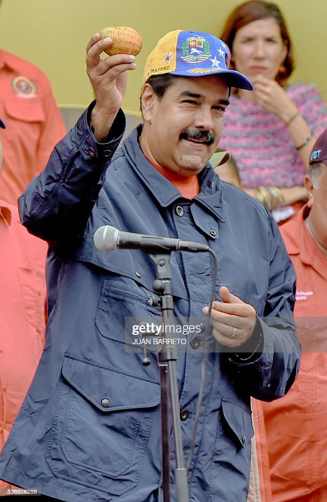 Venezuelan president Nicolas Maduro greets supporters during a march to mark International Workers' Day, in Caracas on May 1, 2016. / AFP / JUAN