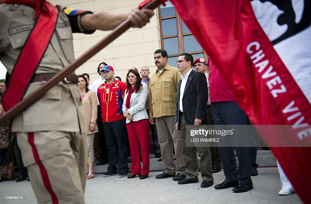 Venezuelan President Nicolas Maduro (2nd R), his wife Cilia Flores (C), and Venezuelan Vice President, Jorge Arreaza (R) pay homage to the late Venezuelan President Hugo Chavez to commemorate five months of his death, at the Cuartel de la Montana in Caracas on August 5, 2013. AFP PHOTO/Leo RAMIREZ