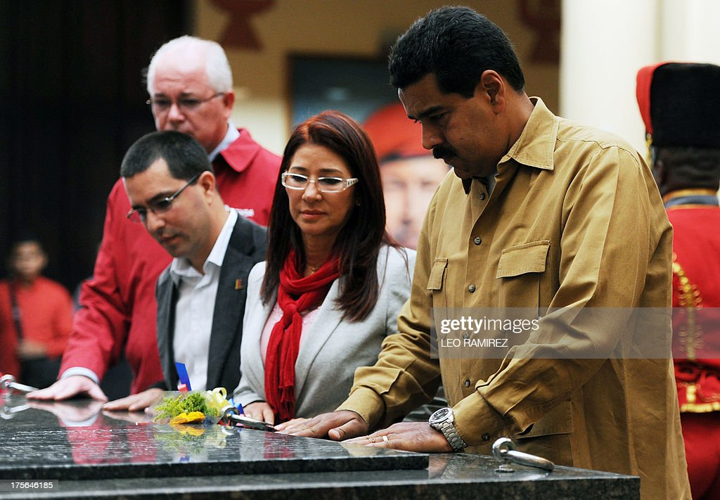 Venezuelan President Nicolas Maduro (R), his wife Cilia Flores (2nd R), Venezuelan Vice President, Jorge Arreaza (2nd L) and PDVSA President Rafael Ramirez (L) pay homage to the late Venezuelan former President Hugo Chavez to commemorate five months of his death, at the Cuartel de la Montana in Caracas on August 5, 2013. AFP PHOTO/Leo RAMIREZ
