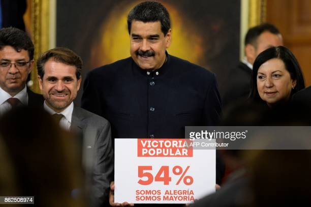 Venezuelan President Nicolas Maduro holds a sign that reads 'popular victory 54 percent we are happiness we are the majority' after a press...