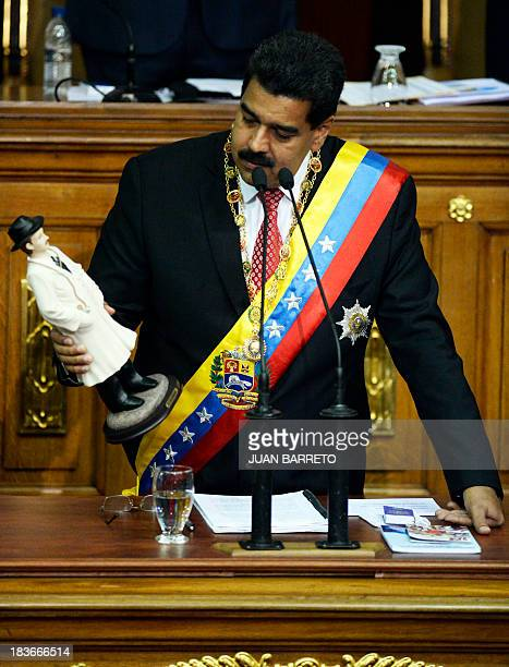 Venezuelan President Nicolas Maduro holds a statuette of Venezuelan medical doctor Jose Gregorio Hernandez at the National Assembly in Caracas on...
