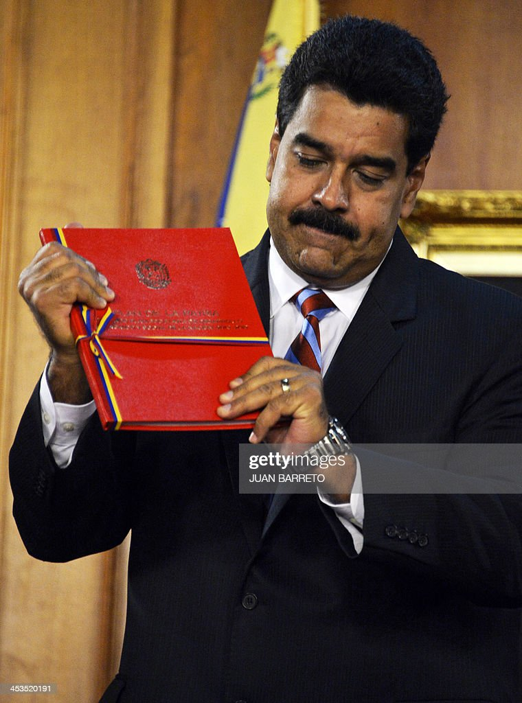 Venezuelan President Nicolas Maduro holds the new law 'Plan de la Patria'--presented by the late president Hugo Chavez during the 2012 presidential campaign-- at the Miraflores presidential palace, in Caracas on December 4, 2013. AFP PHOTO/JUAN BARRETO
