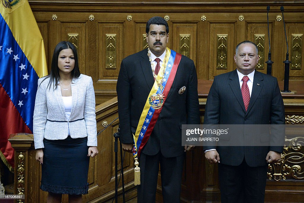 Venezuelan President Nicolas Maduro(C) listens national anthem next to Maria Gabriel Chavez(L) daughter of late Venezuelan president Hugo Chavez and the President of the National Assembly Diosdado Cabello(R) during the Presidential inaguration ceremony in Caracas on April 19, 2013. Nicolas Maduro was sworn in as president of Venezuela on Friday, taking the oath of office in the memory of the late Hugo Chavez to cheers in the National Assembly.