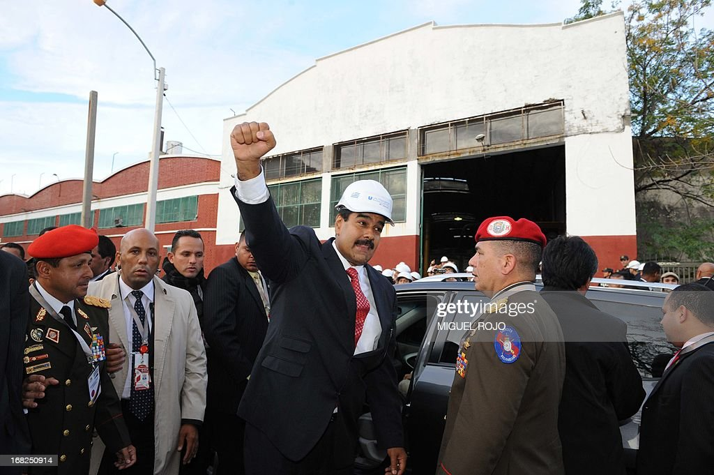 Venezuelan President Nicolas Maduro raises his clenched fist after a visit to the Urutransfor factory in Montevideo, on May 7, 2013. Maduro visits Uruguay as part of a tour that also includes Argentina and Brazil. AFP PHOTO/Miguel ROJO