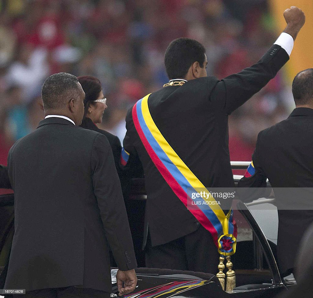 Venezuelan President Nicolas Maduro (R) raises his clenched fist to the crowd during a motorcade after his installation in Caracas on April 19, 2013. AFP PHOTO/Luis Acosta