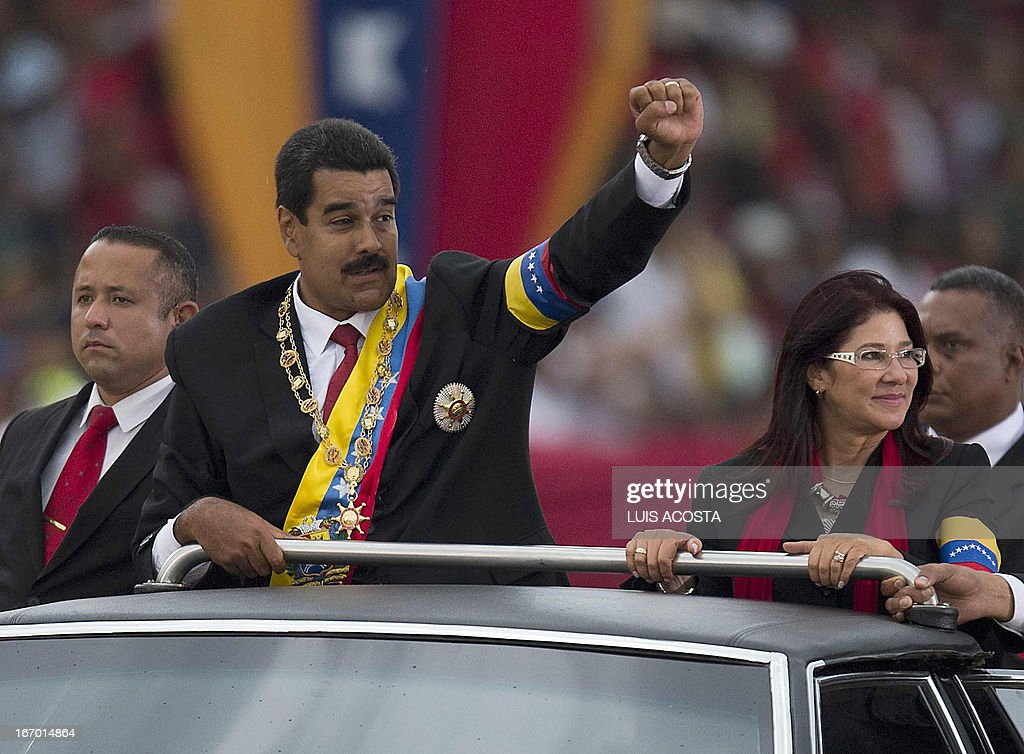 Venezuelan President Nicolas Maduro (C) raises his clenched fist to the crowd during a motorcade after his installation in Caracas on April 19, 2013. AFP PHOTO/Luis Acosta