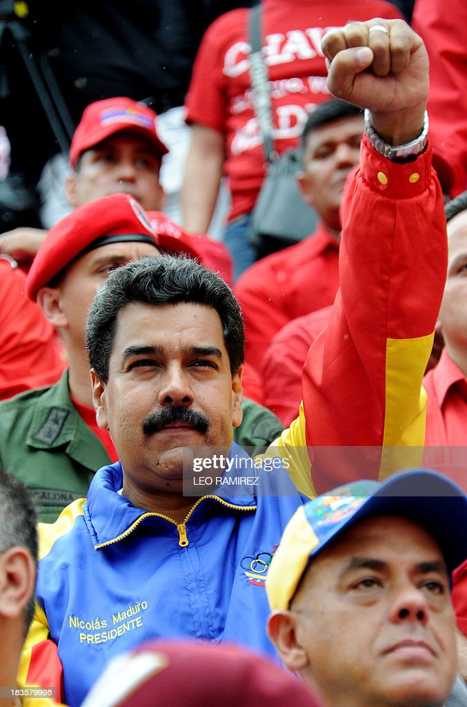 Venezuelan President Nicolas Maduro raises his fist during a ceremony commemorating late President Hugo Chavez re election, in Caracas on October 7, 2013. AFP PHOTO/Leo RAMIREZ