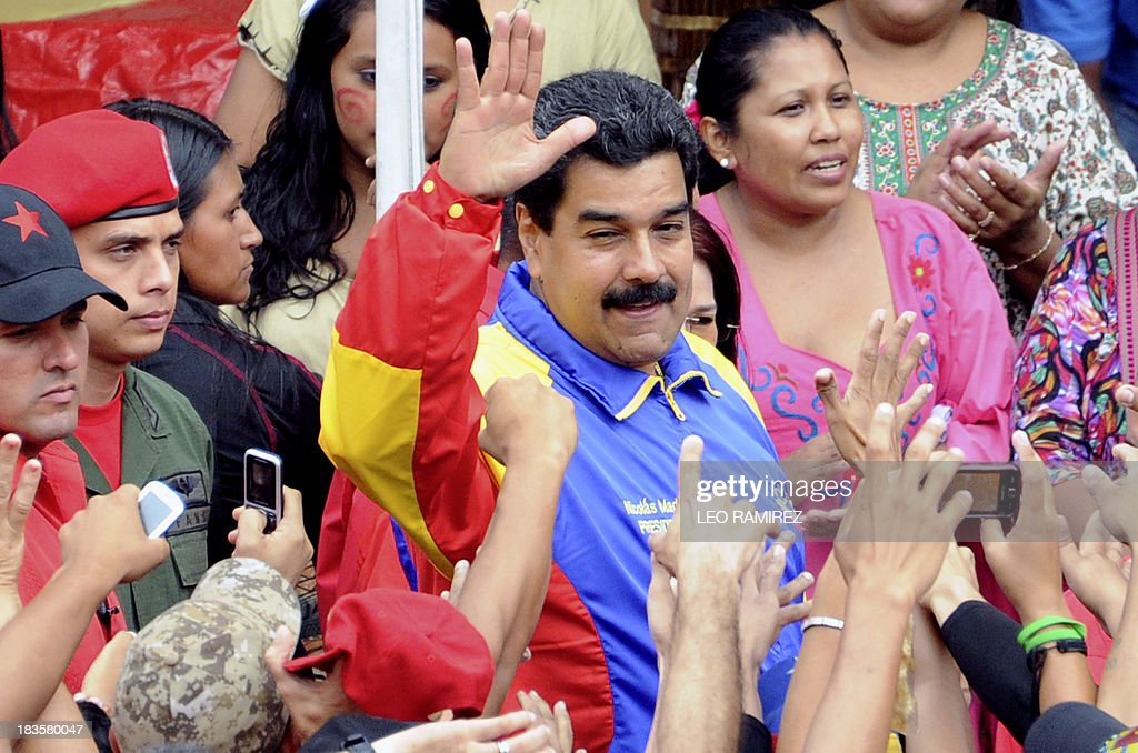 Venezuelan President Nicolas Maduro raises his fist during a ceremony commemorating late President Hugo Chavez re election, in Caracas on October 7, 2013. AFP PHOTO/Leo RAMIREZ