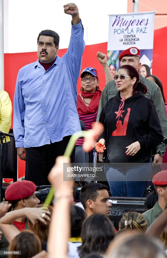 Venezuelan President Nicolas Maduro (L) raises his fist next to First Lady Cilia Flores during a rally with women in Caracas on May 24, 2016. / AFP / JUAN
