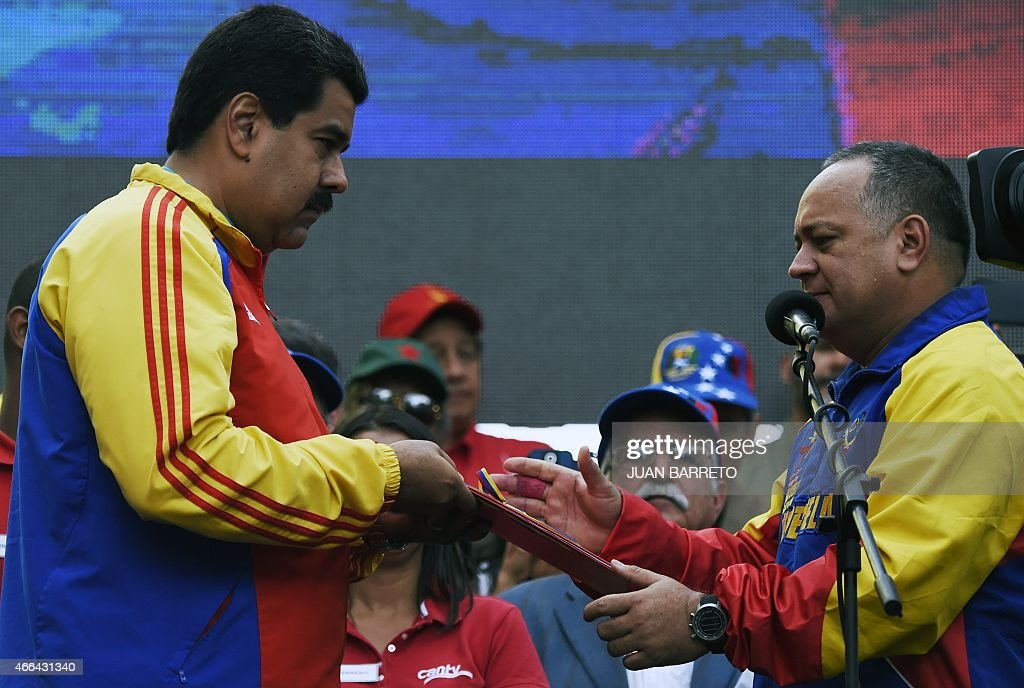 Venezuelan President Nicolas Maduro (L) receives a folder --containing the decree powers law-- from the president of the National Assembly, <a gi-track='captionPersonalityLinkClicked' href=/galleries/search?phrase=Diosdado+Cabello&family=editorial&specificpeople=3799005 ng-click='$event.stopPropagation()'>Diosdado Cabello</a> (R) in Caracas on March 15, 2015. Venezuela's National Assembly voted Sunday to give President Nicholas Maduro decree-making powers in defense and security affairs amid an escalating confrontation with Washington. The special powers were approved by a show of hands in the assembly after two hours of debate and will be in effect for six months.