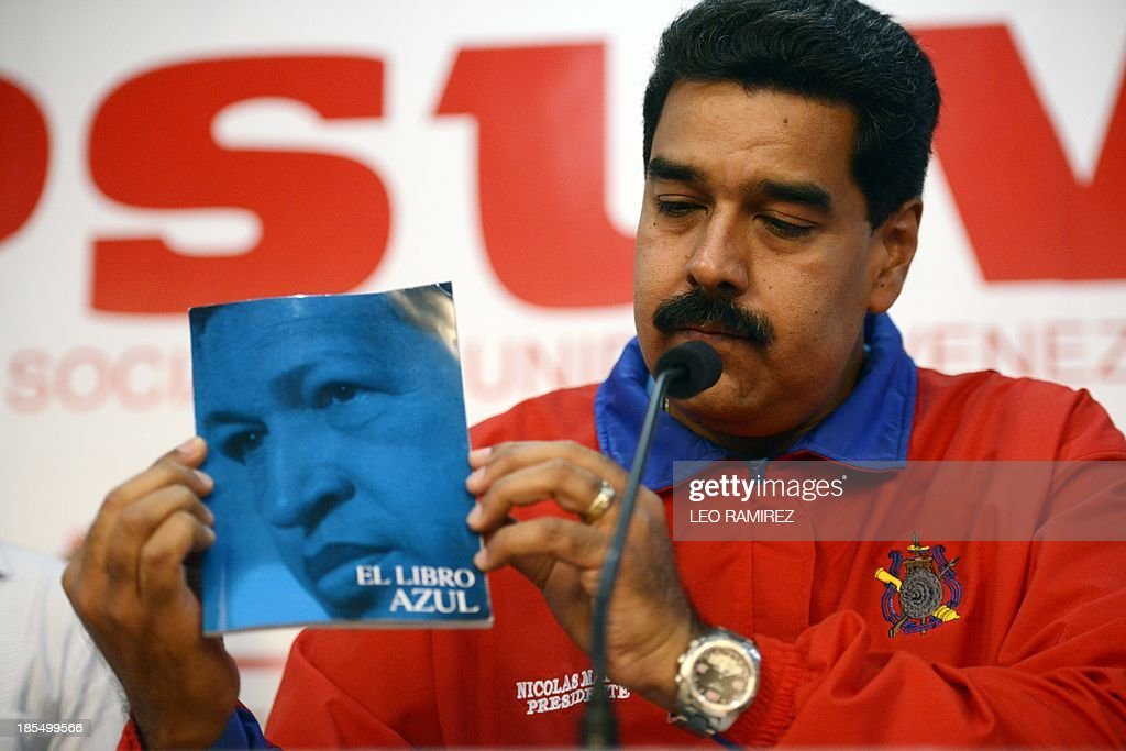 Venezuelan President Nicolas Maduro shows a book of Venezuela former President Hugo Chavez, during a press conference at Venezuela's Socialist Party (PSUV) headquarters in Caracas, on October 21, 2013. AFP PHOTO/Leo RAMIREZ