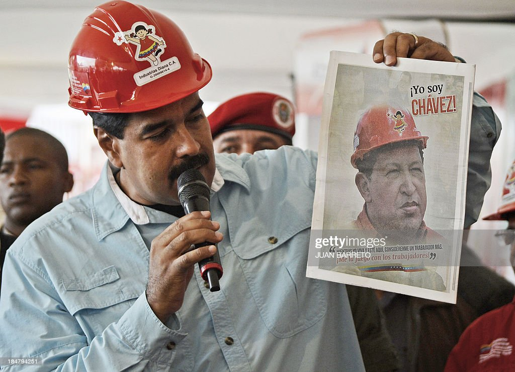 Venezuelan President Nicolas Maduro shows a picture of late President Hugo Chavez during a television program in Caracas on October 16, 2013. Opposition deputies Julio Borges and Nora Bracho were sanctioned Tuesday with 30 days without the right to speak in the National Assembly for challenging loudly Maduro at a meeting last week. AFP PHOTO